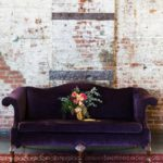 Фиолетовы диван и бордовый ковер
